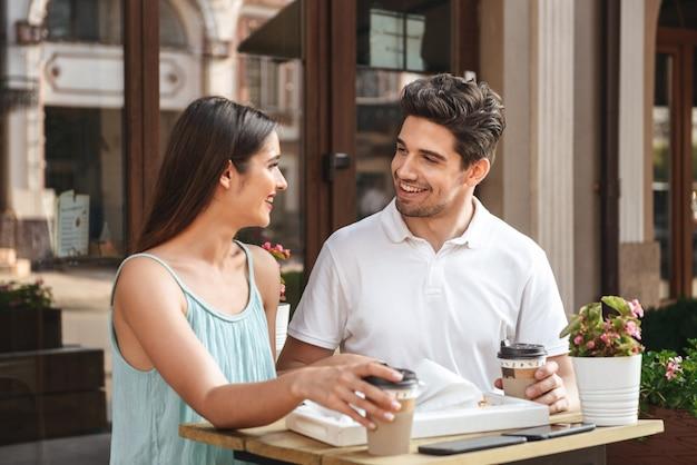 Jeune couple aimant souriant assis dans un café à l'extérieur tout en parlant les uns avec les autres