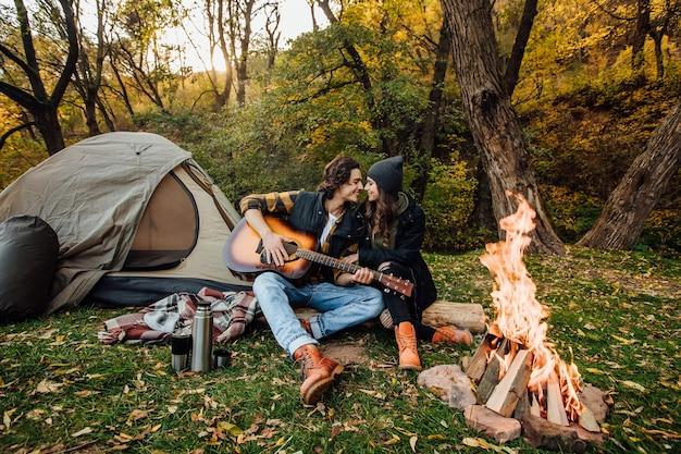 Jeune couple aimant de touristes se détendre près du feu dans la nature