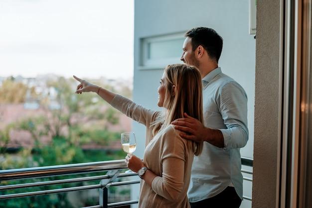 Jeune couple aime boire du vin au balcon. femme montrant quelque chose.