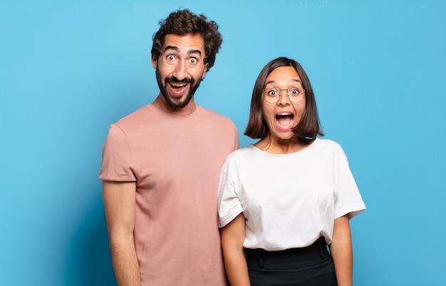 Jeune couple à l'air heureux et agréablement surpris, excité par une expression fascinée et choquée
