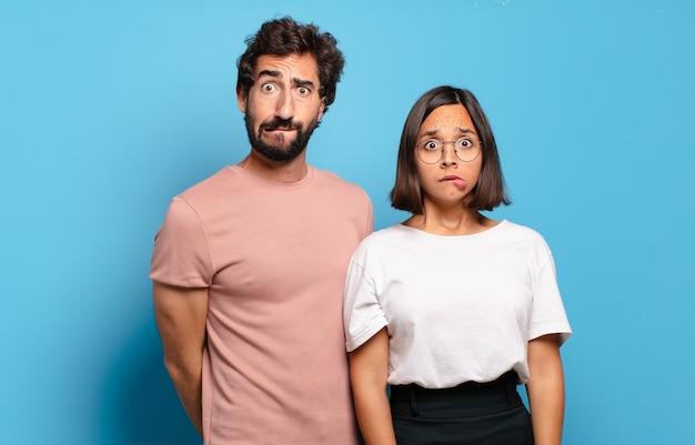 Jeune couple à l'air perplexe et confus, mordant la lèvre avec un geste nerveux, ne connaissant pas la réponse au problème