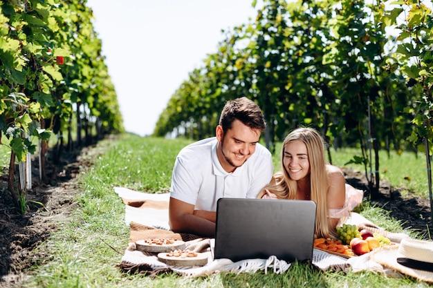 Jeune couple allongé sur une couverture dans le vignoble à la recherche d'un ordinateur portable