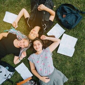 Jeune couple allongé dans un parc avec un livre