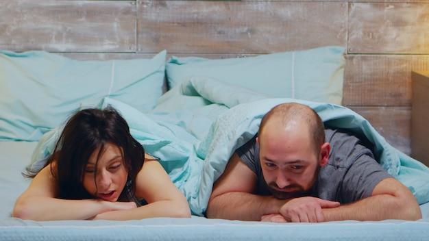 Jeune couple allongé dans son lit en pyjama ayant une conversation.