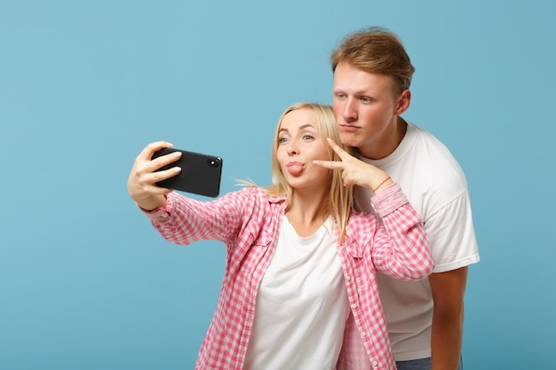 Jeune couple amis homme et femme en t-shirts roses blancs posant