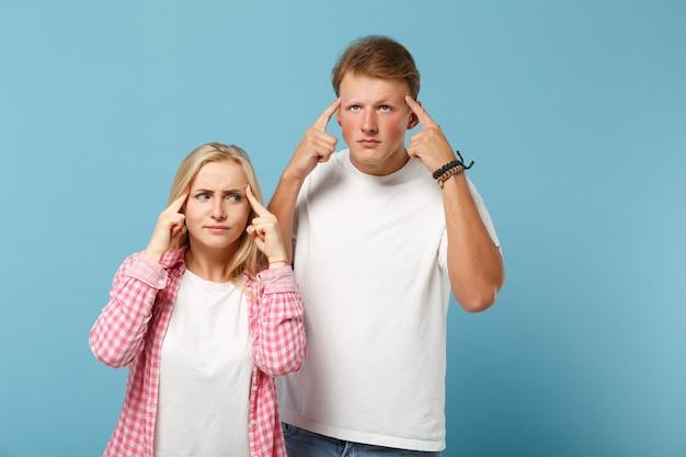 Jeune couple d'amis préoccupés homme et femme en t-shirts blancs vides roses blancs posant