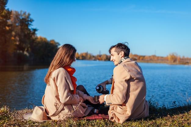 Jeune couple amoureux appréciant le thé au bord du lac en automne