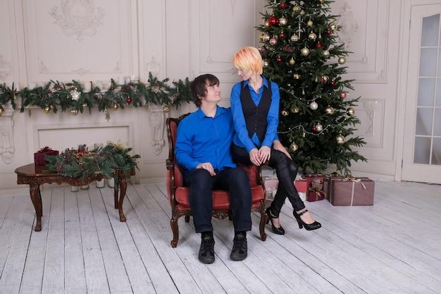 Jeune couple amoureux assis sur un canapé à la maison sur l'arbre de noël en arrière-plan