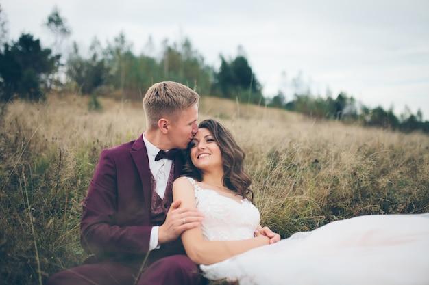 Jeune couple amoureux assis sur l'herbe sur un fond de montagnes, photo de mariage