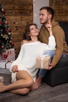 Jeune couple amoureux assis à la maison sur l'arbre de noël sur fond