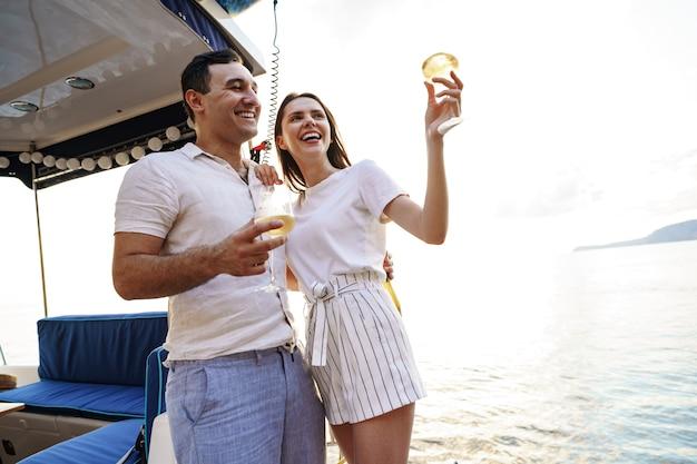 Jeune couple d'amoureux assis sur le pont du yacht et buvant du vin