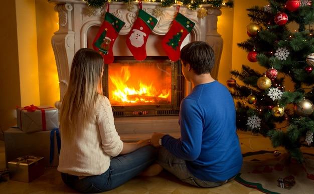Jeune couple amoureux assis près de la cheminée décorée ou noël et regardant le feu