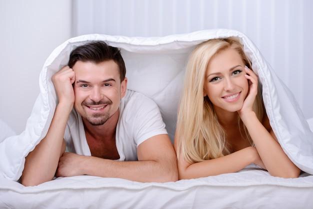 Jeune couple amoureux au lit, sous couvert, souriant à la caméra
