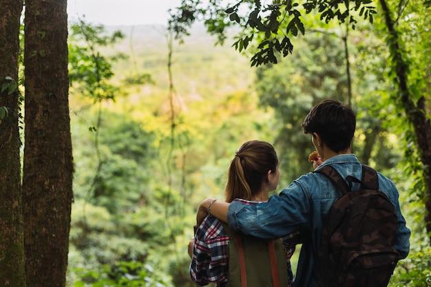 Jeune couple amoureux au parc mangeant une barre de céréales - portrait d'un jeune couple dos à la caméra en admirant la nature.