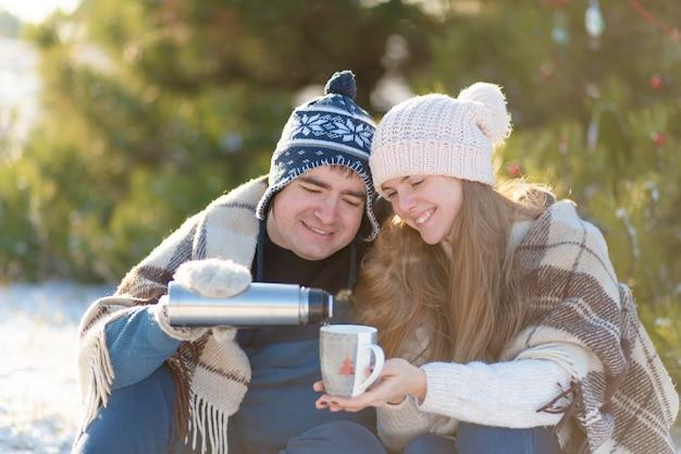 Jeune couple amoureux boire une boisson chaude d'un thermos, assis en hiver dans la forêt, niché dans un endroit chaud