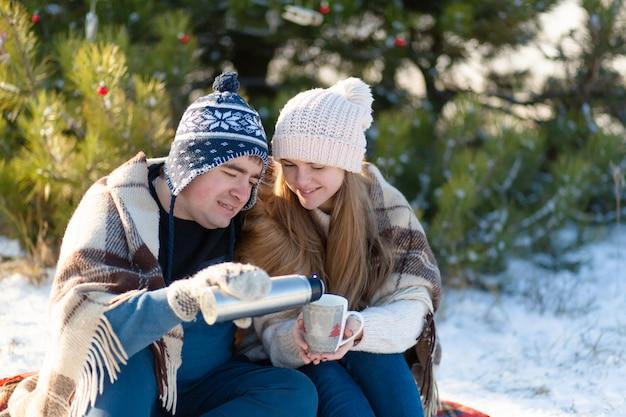 Jeune couple amoureux boire une boisson chaude d'un thermos, assis en hiver dans la forêt