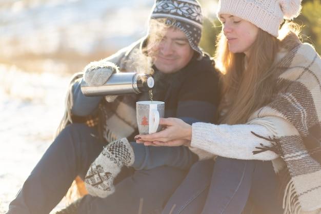 Un jeune couple amoureux boit une boisson chaude dans un thermos, assis en hiver dans la forêt, niché dans des tapis chauds et confortables et profite de la nature. le mec verse un verre d'un thermos dans une tasse