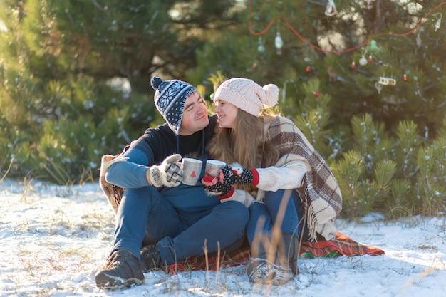 Un jeune couple amoureux boit une boisson chaude avec des guimauves, assis en hiver dans la forêt, niché dans des tapis chauds et confortables et profite de la nature. ils parlent et rient pour une tasse de boisson chaude en forêt