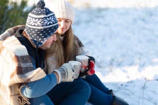 Jeune couple amoureux boit une boisson chaude avec des guimauves, assis en hiver dans la forêt