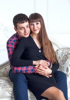 Jeune couple amoureux câlins assis sur le canapé.