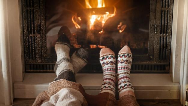 Jeune couple amoureux en chaussettes chaudes tricotées à côté d'une cheminée allumée dans le salon