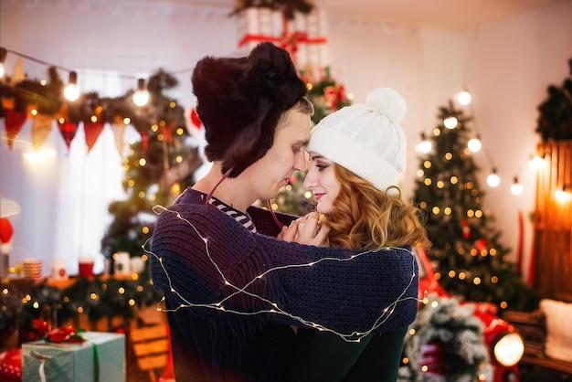 Un jeune couple amoureux contre les arbres de noël avec des guirlandes. un jeune homme dans un chapeau à oreillettes réchauffe les mains d'une belle fille, enveloppée dans une écharpe.