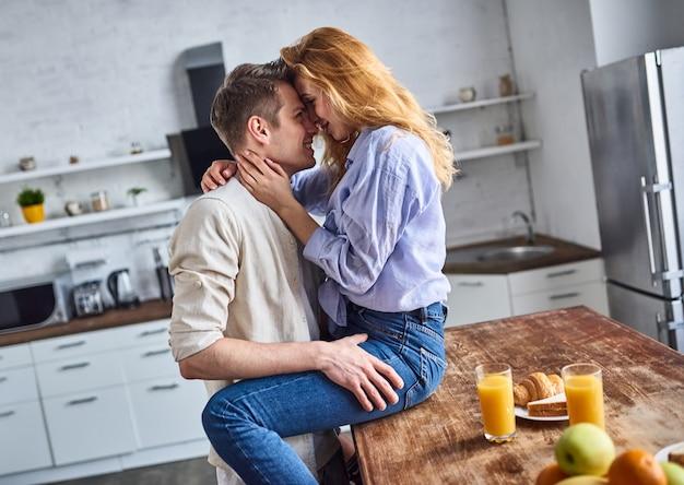 Jeune couple amoureux dans la cuisine. jolie fille assise sur la table et le gars la serre dans ses bras. petit déjeuner romantique.
