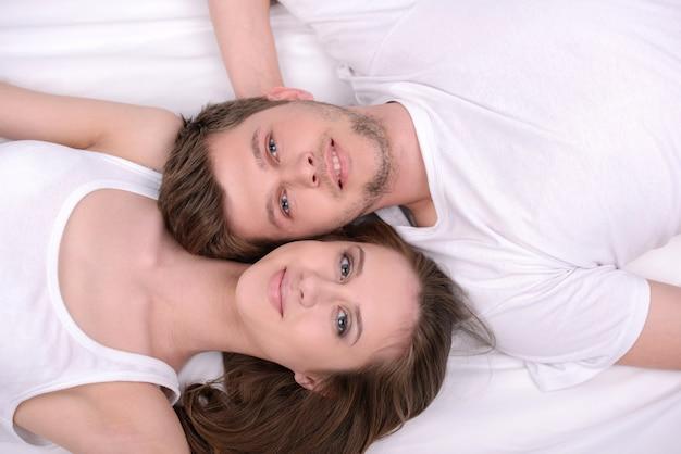 Jeune couple d'amoureux dans un lit blanc.