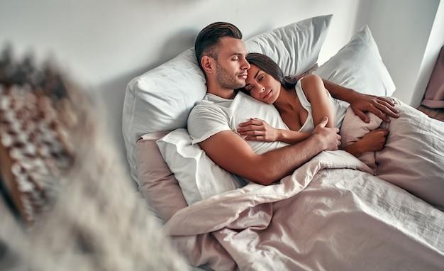 Jeune couple amoureux dort dans son lit dans une étreinte. le matin d'un couple marié.