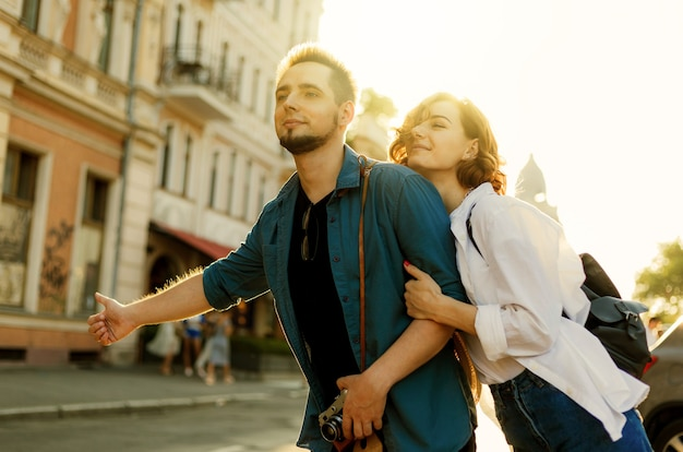 Un jeune couple d'amoureux élégant et heureux attrape une voiture dans la ville. concept d'auto-stop