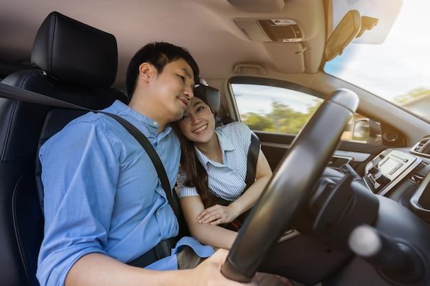 Jeune couple amoureux ensemble en conduisant une voiture