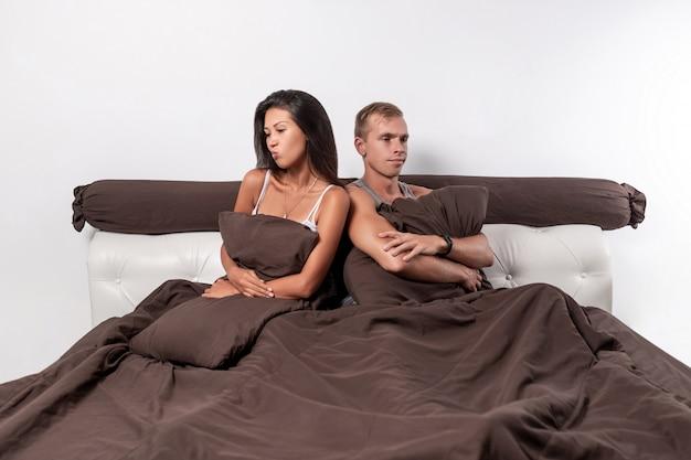 Un jeune couple d'amoureux est assis dans son lit, les bras croisés sur la poitrine