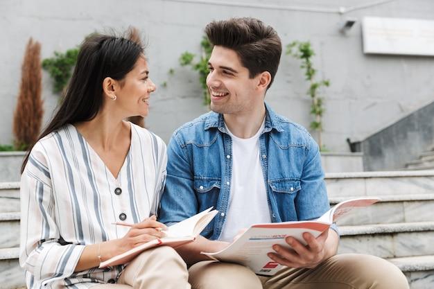 Jeune couple d'amoureux étonnant collègues étudiants à l'extérieur à l'extérieur sur les marches en lisant un livre en écrivant des notes en étudiant.