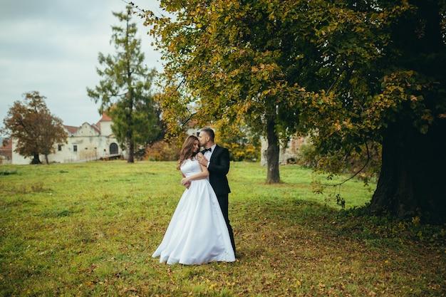 Jeune couple amoureux étreignant sur un ancien château, séance photo de mariage