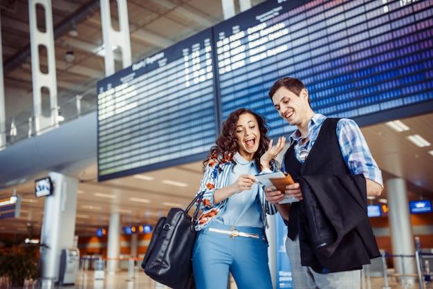 Jeune couple d'amoureux étreignant dans le terminal de l'aéroport.