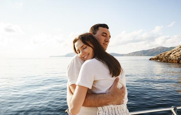 Jeune couple d'amoureux étreignant debout sur le yacht dans la mer