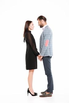 Jeune couple d'amoureux heureux debout isolé