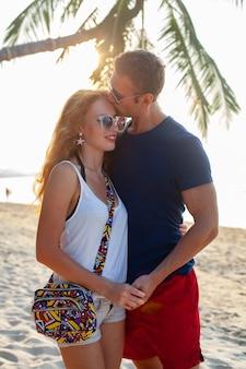 Jeune couple amoureux heureux sur la plage d'été ensemble s'amusant