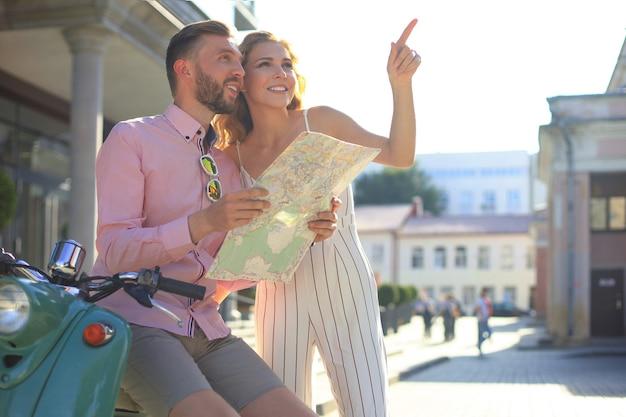 Jeune couple d'amoureux heureux regardant la carte et assis sur un scooter.