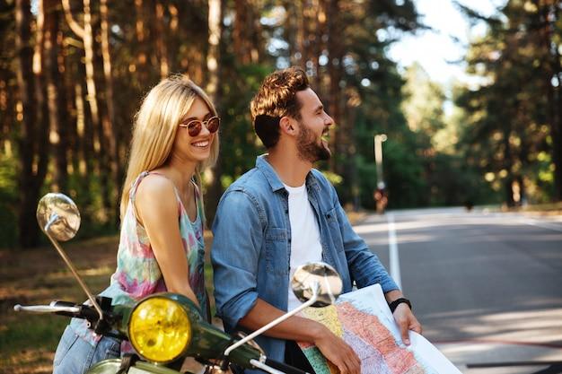 Jeune couple d'amoureux heureux tenant la carte à l'extérieur