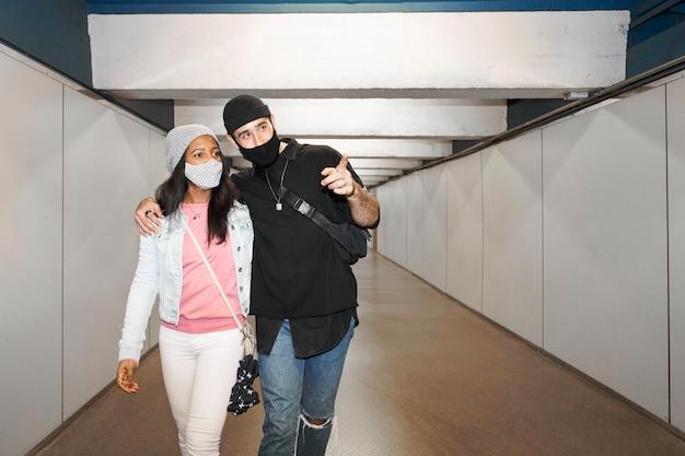Jeune couple d'amoureux interracial dans un couloir de métro souterrain portant des masques faciaux