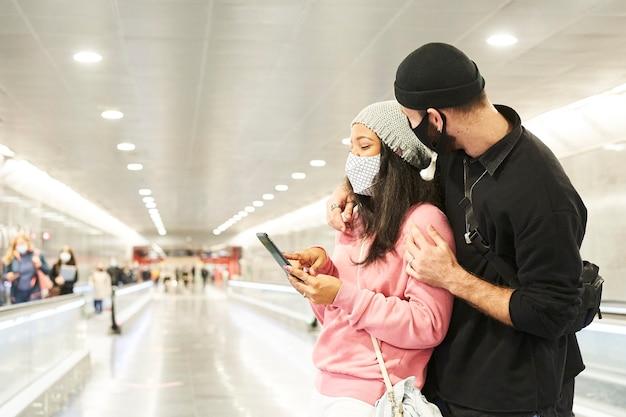 Un jeune couple d'amoureux interracial avec des masques et des chapeaux de laine dans un couloir de métro