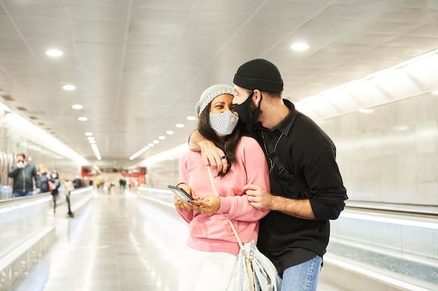 Un jeune couple d'amoureux interracial portant des masques et des chapeaux de laine dans un couloir de métro