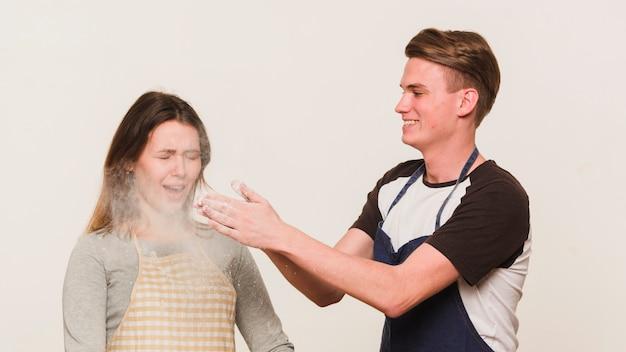 Jeune couple d'amoureux jouant avec de la farine