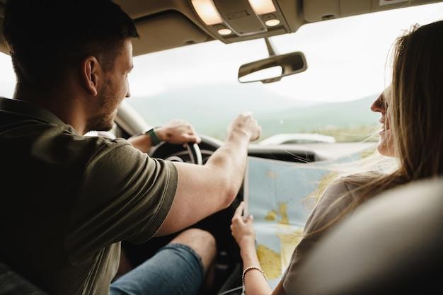 Jeune couple d'amoureux lors d'un voyage sur la route à l'aide d'une carte à l'intérieur d'une voiture, gros plan