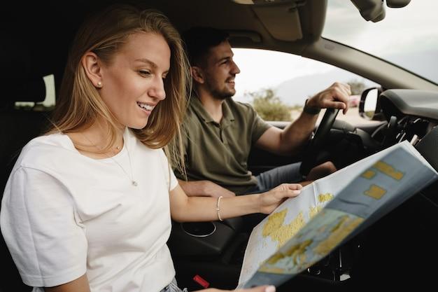 Jeune couple d'amoureux lors d'un voyage sur la route à l'aide d'une carte à l'intérieur d'une voiture