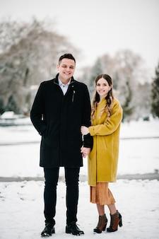 Jeune couple amoureux main dans la main en plein air.