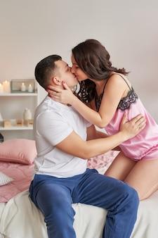 Jeune couple amoureux à la maison sur le lit pour célébrer la saint valentin