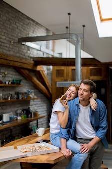Jeune couple amoureux mangeant une pizza dans la maison rustique