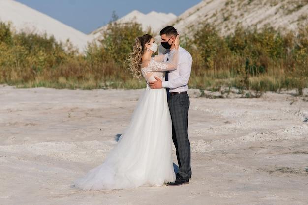 Jeune couple amoureux marchant dans des masques médicaux dans le parc pendant la quarantaine le jour de leur mariage.
